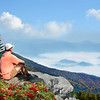 Man siting on a top of mountain, over clouds relaxing, enjoying beautiful foggy mountain landscape on his autumn hiking trip. Copy Space. Near Asheville, Blue Ridge Mountains, North carolina, USA.