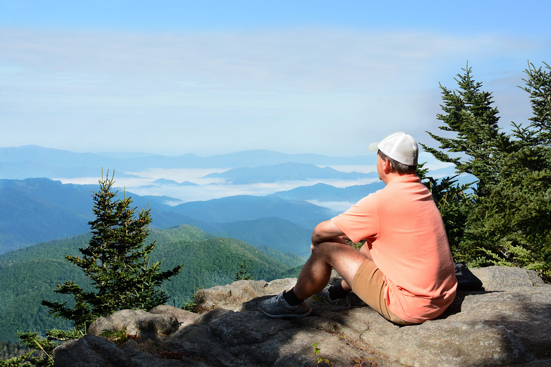 Man with siting on a top of mountain relaxing. and enjoying beautiful summer foggy mountain landscape during his hiking trip. Near Asheville, Blue Ridge Mountains, North carolina, USA.