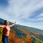 Joy and freedom. Young woman enjoying life outdoors. Smiling, happy girl  with outstretched arms in the autumn  mountain scenery. Blue Ridge Parkway, Close to Blowing Rock, North Carolina,USA.
