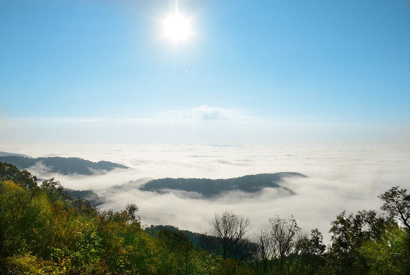 Beautiful mountain landscape with clouds over the mountains and hills at sunrise on sunny autumn morning. Close to Blowing Rock, Blue Ridge Parkway, North Carolina, USA.
