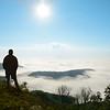 Man standing on a top of the mountain enjoying  beautiful foggy mountain scenery, during his  autumn hiking trip. Close to Blowing Rock, Blue Ridge Parkway, North Carolina, USA.