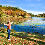 Happiness. Happy girl relaxing outdoors by the lake. Smiling woman with outstretched arms in the autumn  scenery.   Blowing Rock, North Carolina,USA.