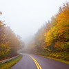 Blue Ridge Parkway on foggy autumn morning, Highway winding through colorful forest. North Carolina, USA.