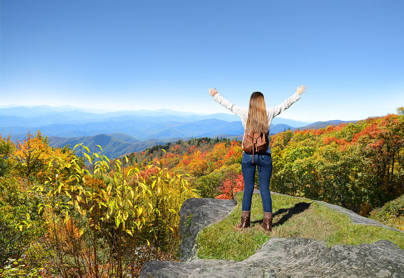 Girl enjoying time on top of the mountain on her fall hiking trip.