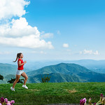 Young woman running along green mountains. Smiling girl exercising on vacation trip. Blue Ridge Parkway, close to Blowing Rock, North Carolina, USA
