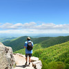 Man with backpack hiking  in mountains on a summer vacation trip.