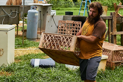 Hayden Smith, co-owner of Gnome Mountain Farms in Franklin, North Carolina, carries a portable chicken crate to the chicken pen, Sunday, June 27, 2021. (Joseph Forzano / Deep Creek Films)