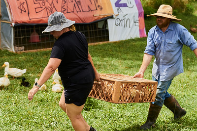Samantha Forzano of Bryson City, North Carolina (left) and Seth (last name withheld), co-owner of Gnome Mountain Farms in Franklin, North Carolina, move a crate of chickens from their pen to the processing area, Sunday, June 27, 2021. (Joseph Forzano / Deep Creek Films)