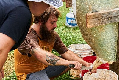 Hayden Smith, co-owner of Gnome Mountain Farms in Franklin, North Carolina (left) shows Samantha Forzano of Bryson City, North Carolina, how to make the cut across the chicken's neck to perform a humane kill on Sunday, June 27, 2021. The cut needs to be precise, so as to avoid cutting the windpipe.  (Joseph Forzano / Deep Creek Films)