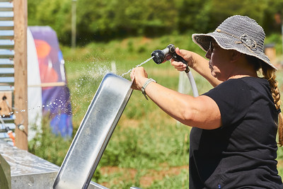 Samantha Forzano of Bryson City, North Carolina, cleans the evisceration table at Gnome Mountain Farms in preparation for chicken processing, Sunday, June 27, 2021. (Joseph Forzano / Deep Creek Films)