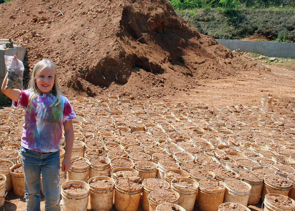 Betsy with her treasures standing in front of the buckets of earth like we used to find our gems
