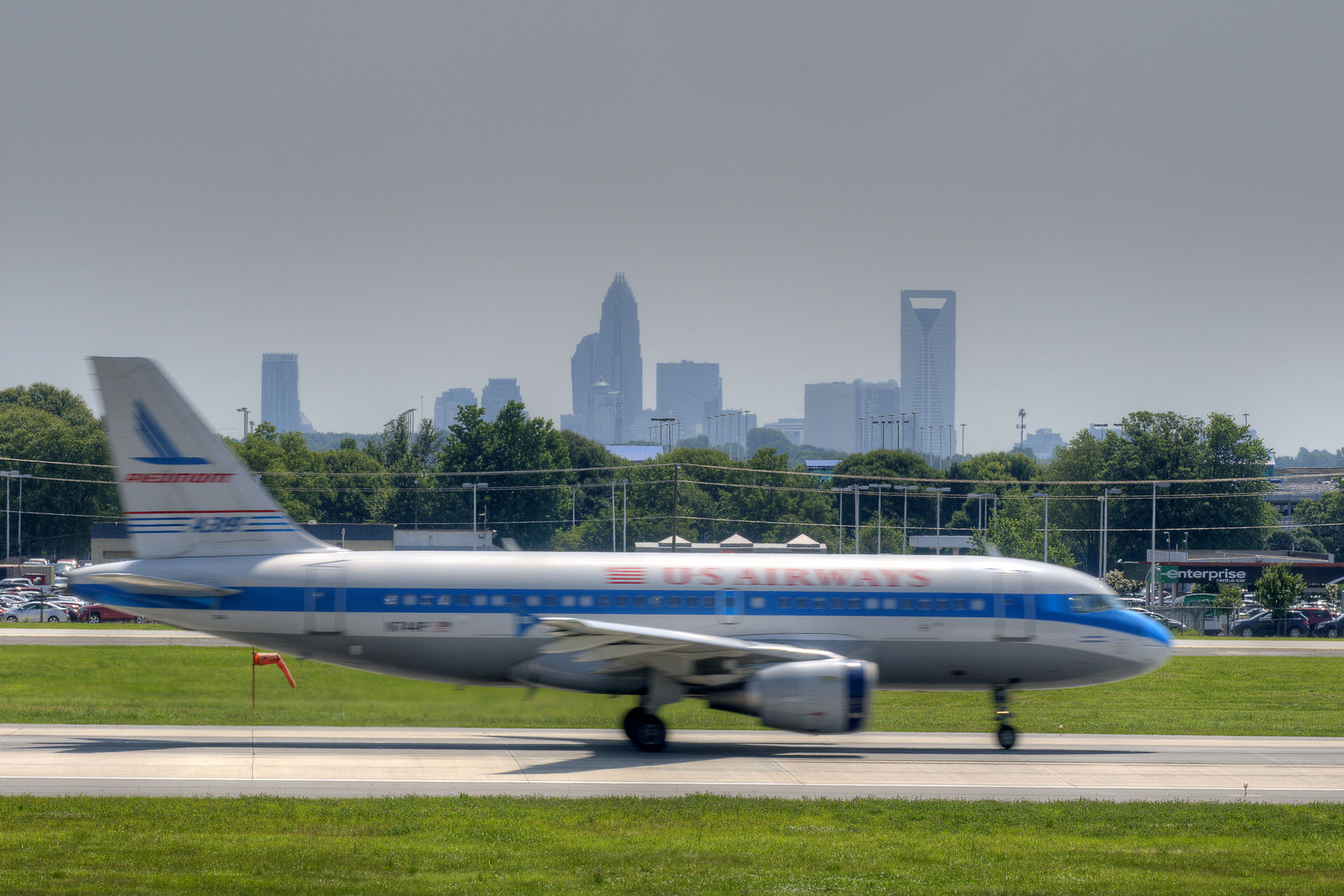An US Airways Airbus A320 takes off with a view of Uptown Charlotte in the distance at the Airport Observation Park at Charlotte-Douglas International Airport in Charlotte, NC on Sunday, June 15, 2014. Copyright 2014 Jason Barnette