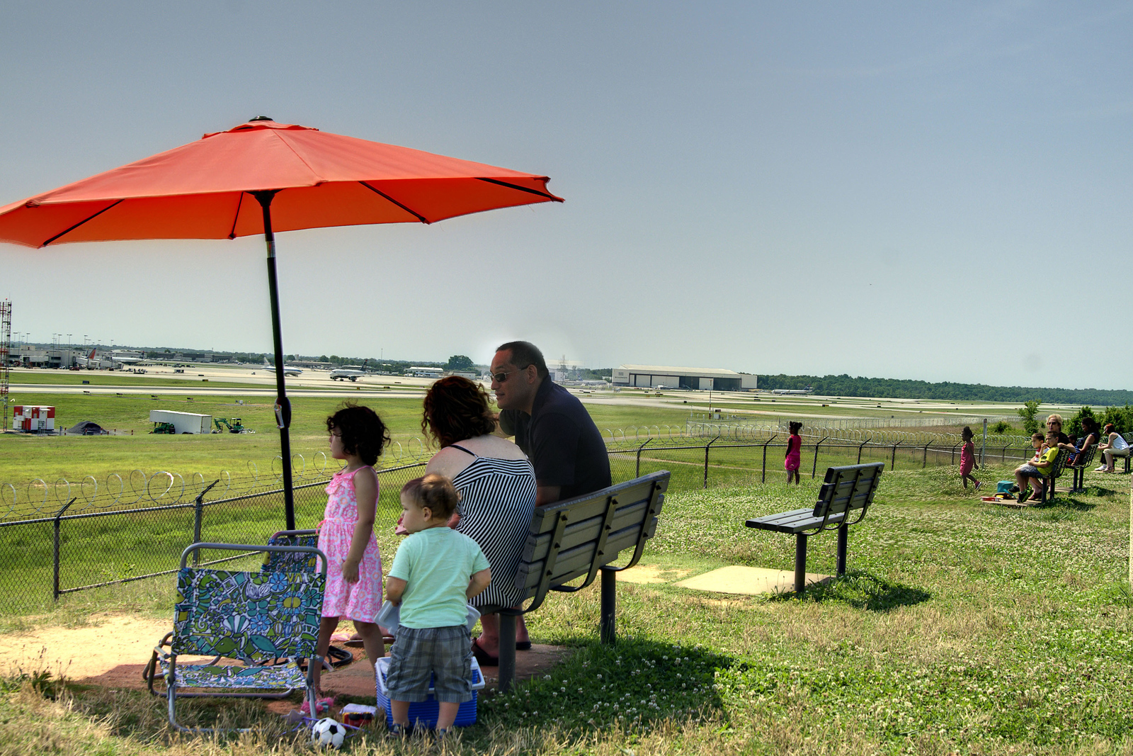 Families have picnics and sit under the shade of umbrellas while watching planes land and take off at the Airport Observation Park at Charlotte-Douglas International Airport in Charlotte, NC on Sunday, June 15, 2014. Copyright 2014 Jason Barnette