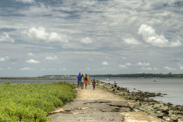 A family walks across The Rocks, a seawall built in the late 1800s to prevent erosion into the Cape Fear River, at the Fort Fisher State Recreation Area on the southern tip of Pleasure Island in Kure Beach, NC on Saturday, July 12, 2014. Copyright 2014 Jason Barnette