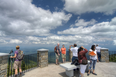 Visitors stretch their legs, chat with friends, and snap photos from the observation deck atop Mt. Mitchell in Mount Mitchell State Park at Milepost 355.4 on the Blue Ridge Parkway in NC on Saturday, June 15, 2013. Copyright 2013 Jason Barnette