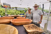 Husband and wife team Van and Kim Owens pose inside their booth with carved wooden bowls at Franklin Square Park during the North Carolina 4th of July Festival in Southport, NC on Friday, July 3, 2015. Copyright 2015 Jason Barnette