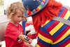 A clown paints an American flag onto a boy's arm at Franklin Square Park during the North Carolina 4th of July Festival in Southport, NC on Friday, July 3, 2015. Copyright 2015 Jason Barnette