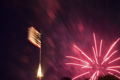 The fireworks explode behind an American flag fluttering in the strong breeze during the North Carolina 4th of July Festival in Southport, NC on Saturday, July 4, 2015. Copyright 2015 Jason Barnette