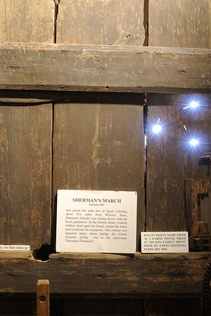 Three bullet holes (illuminated using a flash from behind) created in the front door of the Nelson's home by Union soldiers during the Civil War in 1865, now on display at the Museum of the Waxhaws in Waxhaw, NC on Saturday, June 14, 2014. Copyright 2014 Jason Barnette