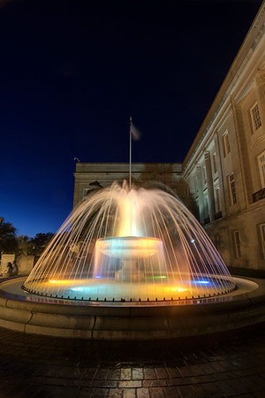 A multi-colored water fountain churns in front of the Alton Lennon Federal Building on Water Street in downtown Wilmington, NC on Sunday, July 13, 2014. Copyright 2014 Jason Barnette