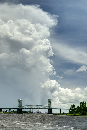 A towering summer thunderstorm looms over the sky beyond the Cape Fear Memorial Bridge in Wilmington, NC on Sunday, July 13, 2014. Copyright 2014 Jason Barnette
