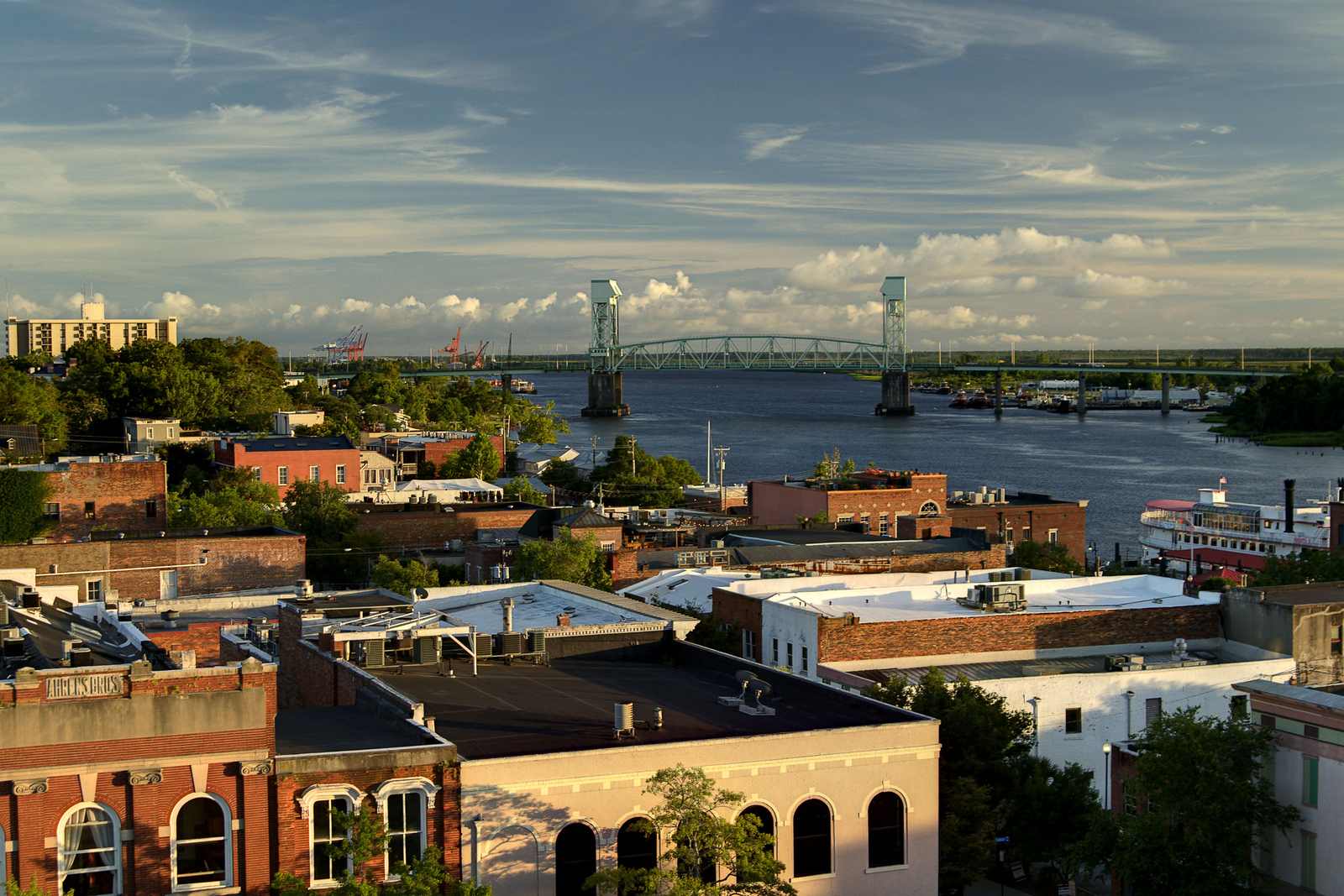 A view along the rooftops of buildings in the historic downtown district toward the Cape Fear Memorial Bridge in Wilmington, NC on Sunday, July 13, 2014. Copyright 2014 Jason Barnette