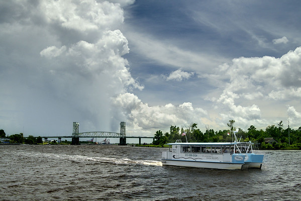 A tour boat sets course up the Cape Fear River as a towering summer thunderstorm covers the sky beyond the Cape Fear Memorial Bridge in Wilmington, NC on Sunday, July 13, 2014. Copyright 2014 Jason Barnette