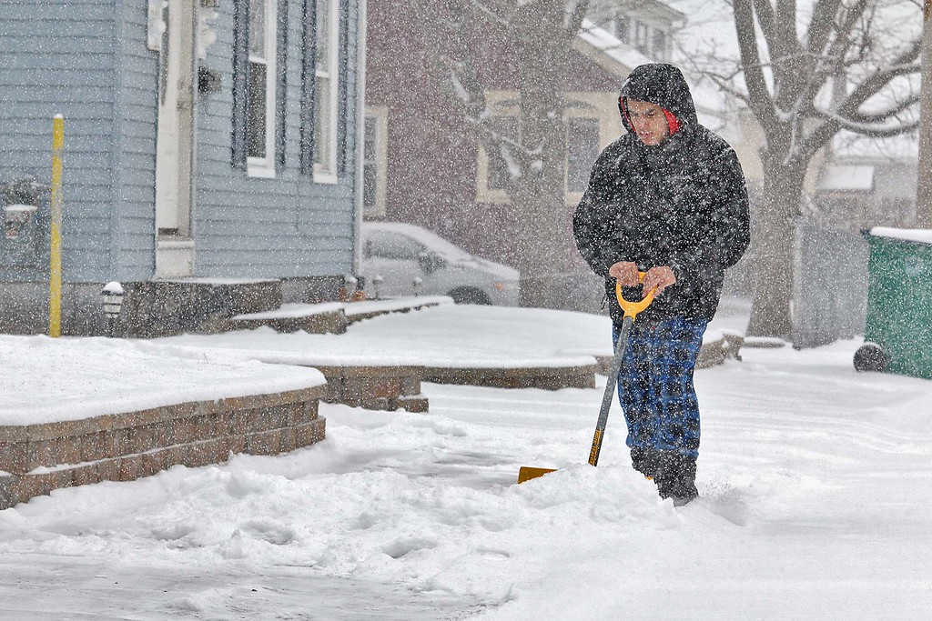 . Steven Alejandro, 19, clears the snow off the sidewalk in front of his home on Lincoln Street in Fitchburg during Wednesday\'s storm. SENTINEL & ENTERPRISE/JOHN LOVE