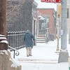 A pedestrian walks up Main Street in Fitchburg towards the boulder during Wednesday's storm. SENTINEL & ENTERPRISE/JOHN LOVE