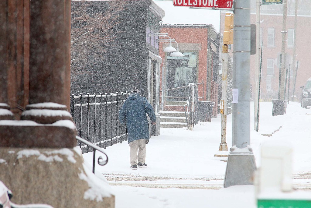 . A pedestrian walks up Main Street in Fitchburg towards the boulder during Wednesday\'s storm. SENTINEL & ENTERPRISE/JOHN LOVE