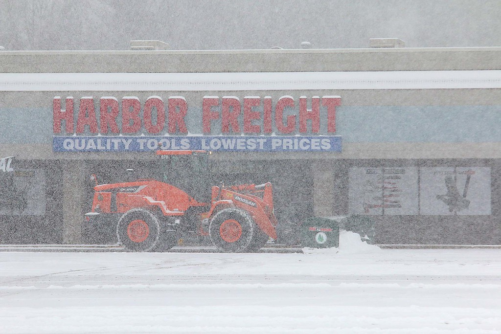 . A plow clears snow in the parking lot in front of Harbor Freight on John Fitch Highway during Wednesday\'s storm. SENTINEL & ENTERPRISE/JOHN LOVE