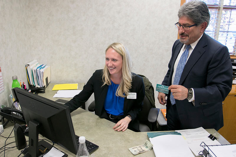 Fitchburg Mayor Stephen DiNatale gets his new North Central Massachusetts Chamber of Commerce gift card set up by Lauren Goulet the Chambers office manager after the press conference to tell everyone about it on Tuesday afternoon. SENTINEL & ENTERPRISE/JOHN LOVE