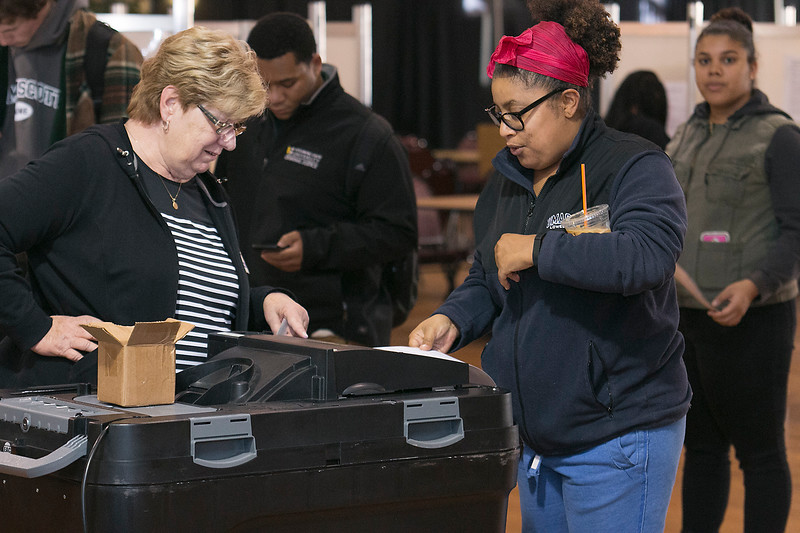 Judy Normandin the clerk for Ward 4A watches as voter Danielle Cole puts her ballot into the voting box at the polls in the Fitchburg Senior Center on Tuesday morning. SENTINEL & ENTERPRISE/JOHN LOVE
