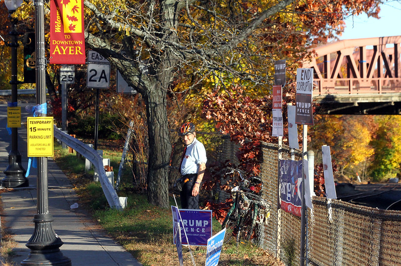 Ayer town resident Frank Maxant stands with array of poll signs across the street from the Ayer Town Hall where voting is taking place, Maxant had just replaced his signs that had been damaged earlier. Nashoba Valley Voice Photo by David H. Brow.