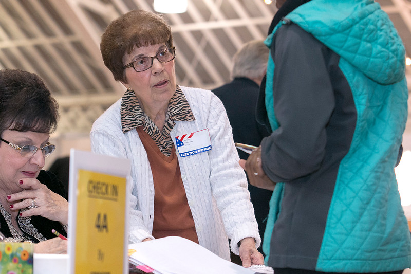 Inspector for Ward 4A Florence Volpe helps out a voter as they check in at the polls at the Fitchburg Senior Senior Center on Tuesday morning. SENTINEL & ENTERPRISE/JOHN LOVE