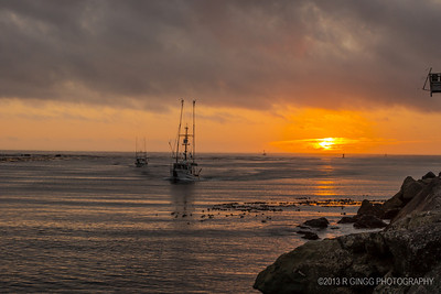Fishing boats coming into Fort Bragg Harbor at Sunset.