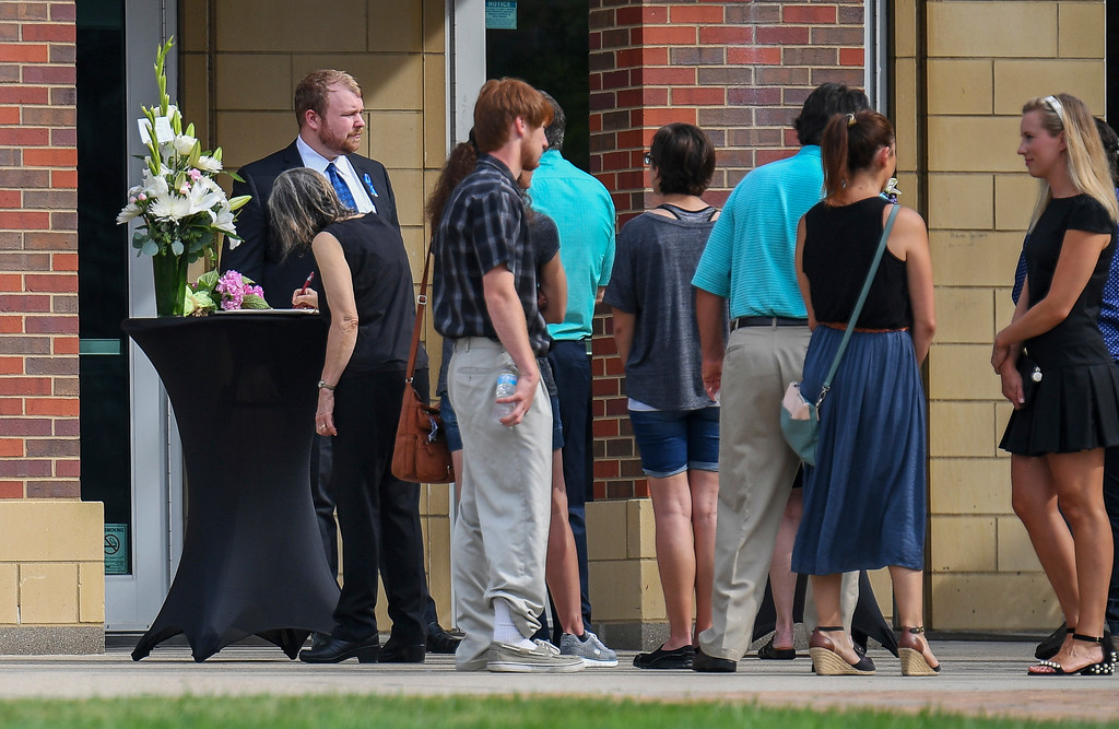 . Mourners, turned away at the door after the service was full to capacity, sign a book on condolences outside of the funeral of Otto Warmbier, Thursday, June 22, 2017, in Wyoming, Ohio. Warmbier, a 22-year-old University of Virginia undergraduate student who was sentenced in March 2016 to 15 years in prison with hard labor in North Korea, died this week, days after returning to the United States. (AP Photo/Bryan Woolston)