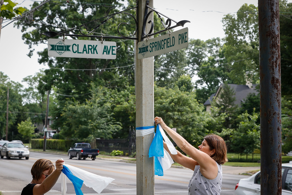 . Denise Koesterman, right, and Alison Lebrun, left, tie blue-and-white awareness ribbons along Springfield Pike near the family home of Otto Warmbier, a 22-year-old University of Virginia undergraduate student who was imprisoned in North Korea in March 2016, in the Wyoming suburb of Cincinnati on Tuesday, June 13, 2017. Warmbier, serving a 15-year prison term for alleged anti-state acts, was released and medically evacuated from the reclusive country Tuesday and has been in a coma for months, his parents said. (AP Photo/John Minchillo)