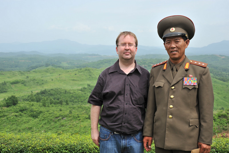 Looking over the DMZ with a North Korean lieutenant.  The UN military is on the mountain behind us (Concrete wall lookout post)