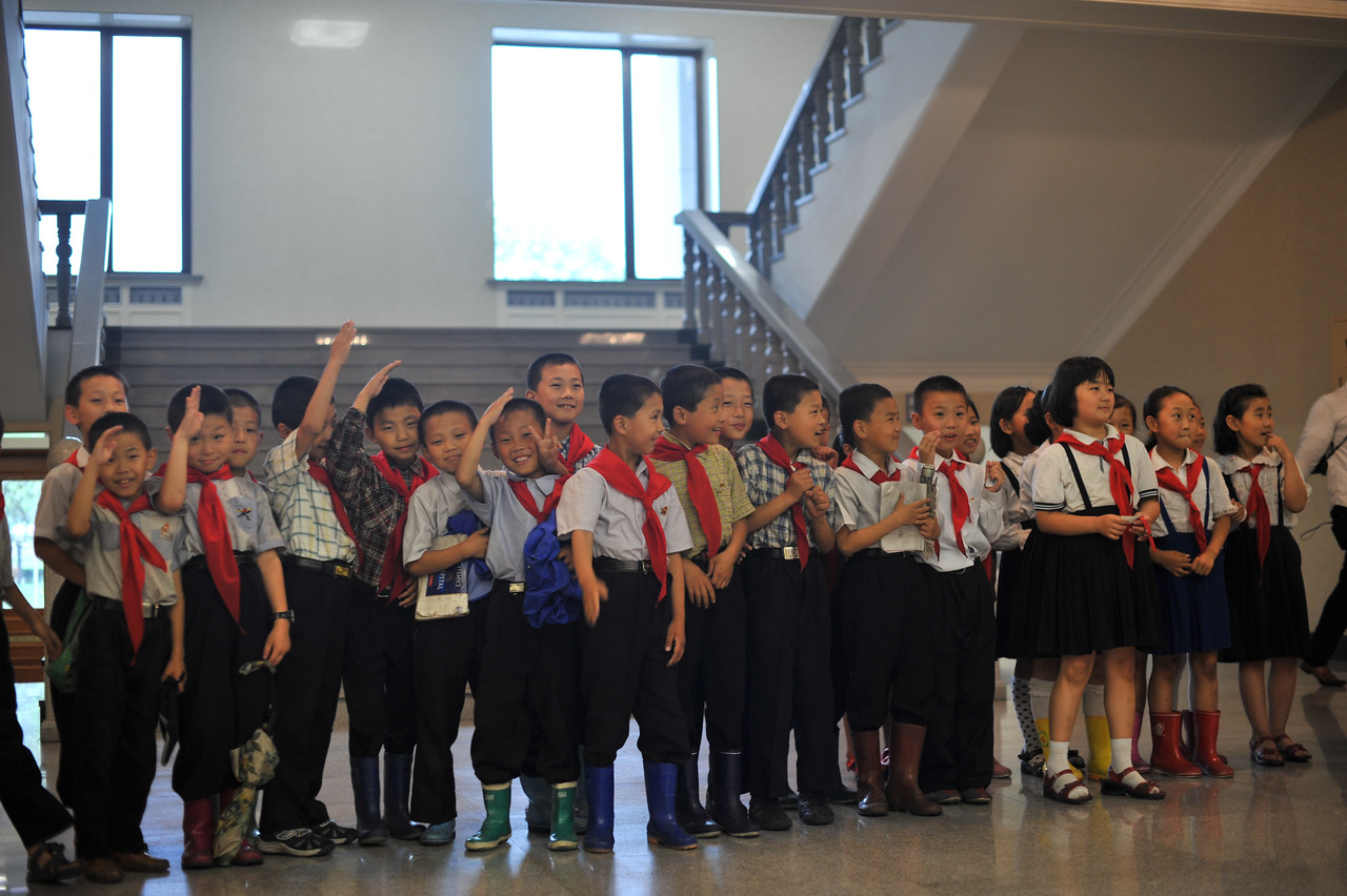 Young pioneers in the Pyongyang Grand Theater.  Some of the kids are giving the pioneer salute.