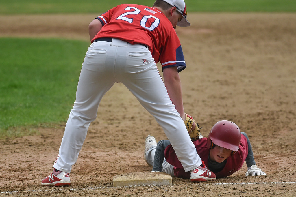 . Zach Scott of Fitchburg (right) slides back to first as North Middlesex first baseman Josh Burneman attempts to pick him off during Monday\'s varsity baseball match up between Fitchburg and North Middlesex at Fitchburg High School.  SENTINEL & ENTERPRISE JEFF PORTER