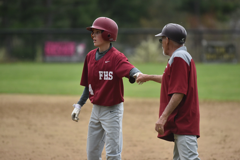 . Zach Scott of Fitchburg celebrates a single with coach during Monday\'s varsity baseball match up between Fitchburg and North Middlesex at Fitchburg High School.  SENTINEL & ENTERPRISE JEFF PORTER