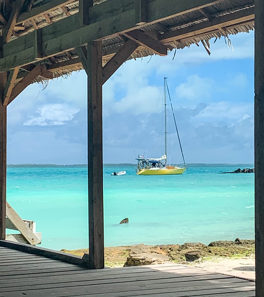 A thatch roof hut frames the scene of a yellow sailboat in the turquoise lagoon.
