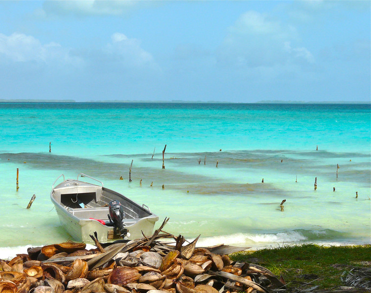 A motorboat sits at the edge of the lagoon. Copra shells are piled behind it.