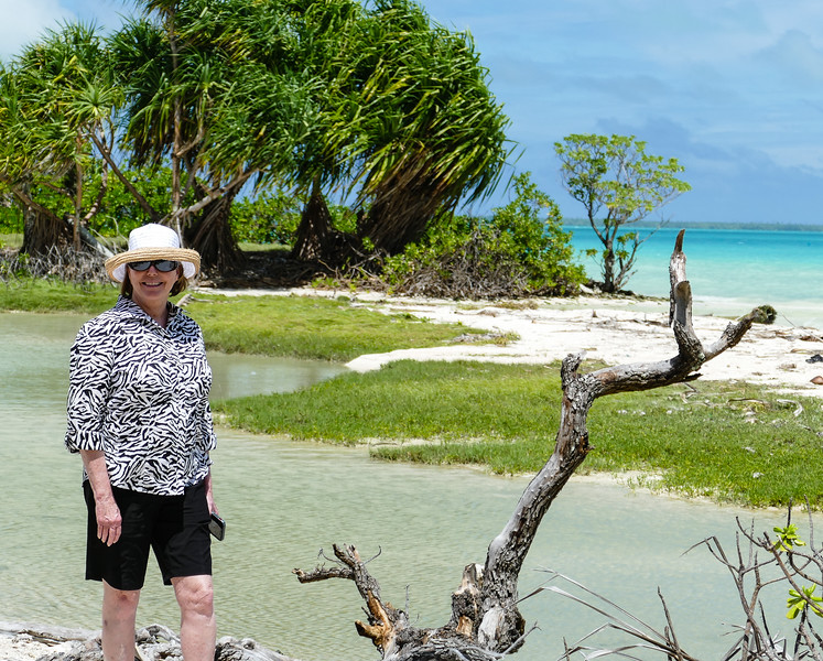 A boomer woman is dressed for a tropical cruise excursion as she stands next to the turquoise lagoon on Taubuaeran Atoll