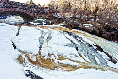 An early spring fills Amity Creek with snow melt that cascades past one of the bridges on Seven Bridges Road.