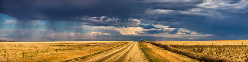 A well deserved rain storm can be seen in the distance from a dirt road near Brookings, South Dakota.