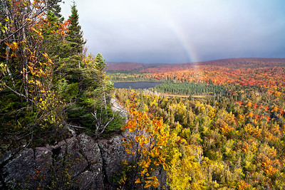 A rainbow shoots up from the blanket of North Shore fall color below Oberg Mountain as viewed at the end of September 2011.  Forest fires raging in the Arrowhead contributed to the ominous skies.