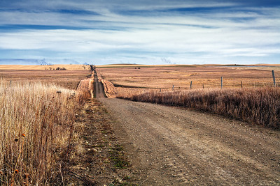 Burning ditches can be seen on the horizon at the end of this lonely prairie dirt road in South Dakota.