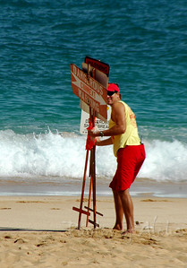 A smile from the lifeguard when he notices I'm shooting him as he puts out warning signs along the dangerous shoreline on a winter day North Shore of O'ahu, Hawai'i